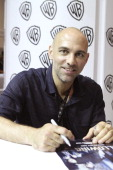 In this handout photo provided by WBTV 'The Following' executive producer Marcos Siega signs autographs for fans in the Warner Bros booth during...