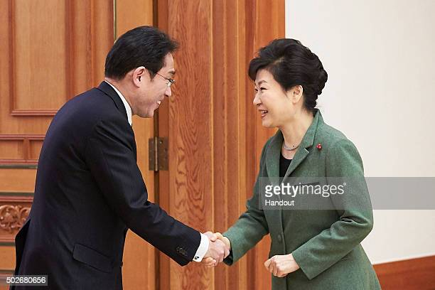 In this handout photo released by the South Korean Presidential Blue House South Korea's President Park GeunHye shakes hands with Japanese Foreign...