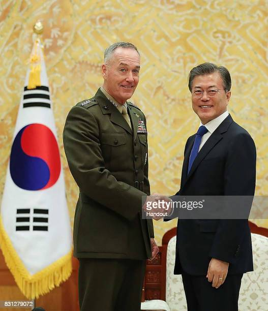 In this handout photo released by the South Korean Presidential Blue House South Korean President Moon Jaein shakes hands with US Chairman of the...