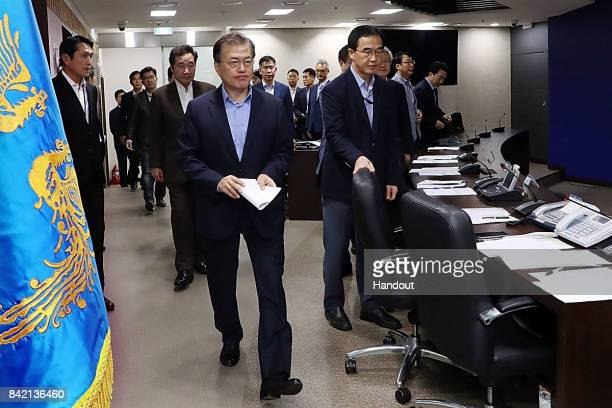In this handout photo released by the South Korean Presidential Blue House South Korean President Moon Jaein arrives for the meeting of the National...