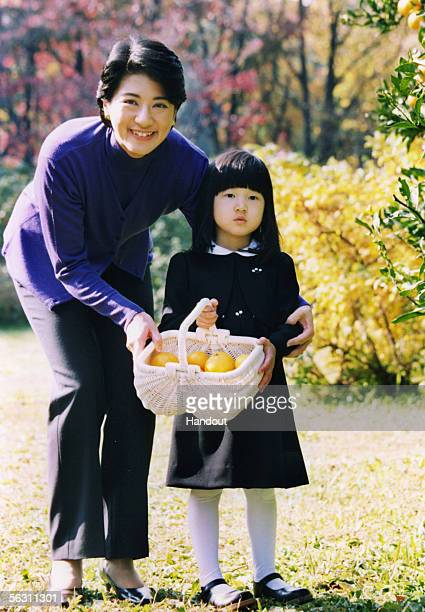 In this Handout Photo released on December 1 2005 by the Imperial Household Agency Japan's Princess Aiko picks mandarin oranges with her mother Crown...