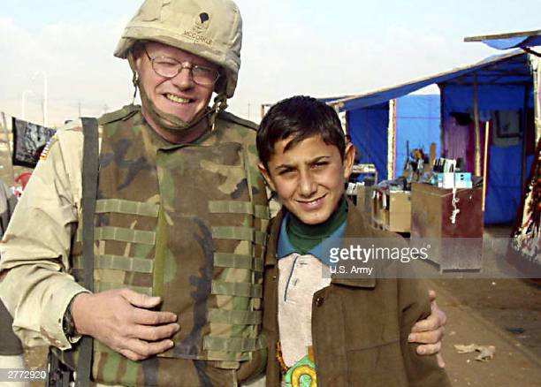 In this handout photo Spc David McCorkle of the 318th Tactical Psychological Operations Battalion poses with an orphaned Iraqi boy near the shop...