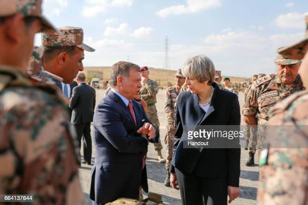 In this handout photo supplied by the Jordanian Royal Palace King Abdullah II of Jordan talking to British Prime Minster Theresa May during their...