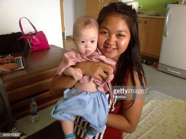 In this handout photo Thai surrogate mother Pattaramon Chanbua poses with baby Gammy at the Samitivej Hospital on August 6 2014 in Chonburi province...