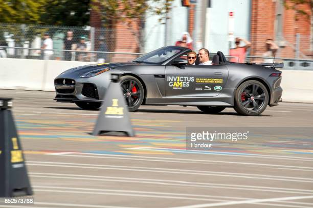 In this handout photograph provided by Jaguar Land Rover via the Brooklyn Brothers Prince Harry drives with German competitor Dennis Siesing during...