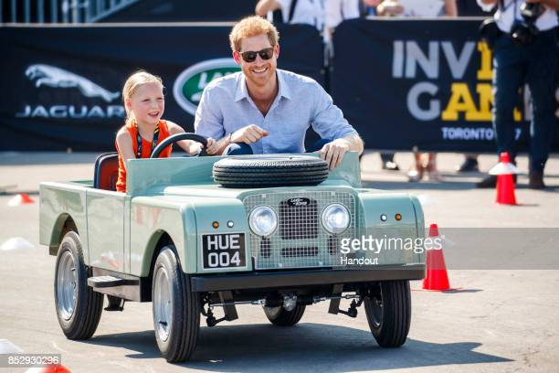 In this handout photograph provided by Jaguar Land Rover via the Brooklyn Brothers Prince Harry drives with five year old Daimy Gommers daughter of...