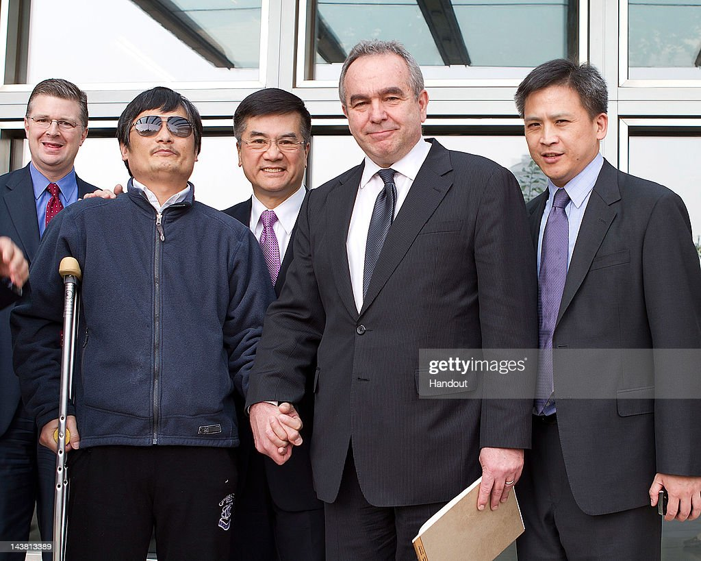 In this handout photograph provided by the US Embassy Beijing press office Chinese dissident Chen Guangcheng holds hands with Assistant Secretary of...