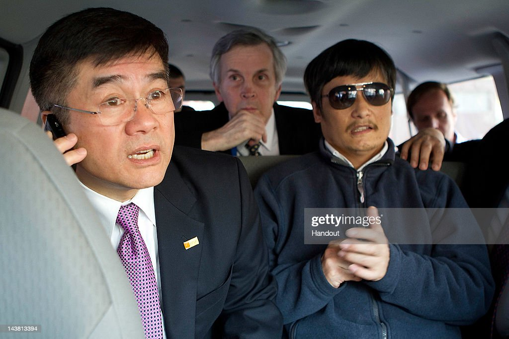 In this handout photograph provided by the US Embassy Beijing press office Chinese dissident Chen Guangcheng looks on as US Ambassador to China Gary...
