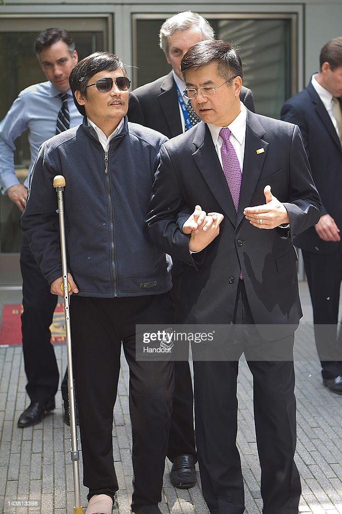 In this handout photograph provided by the US Embassy Beijing press office Chinese dissident Chen Guangcheng talks with US Ambassador to China Gary...