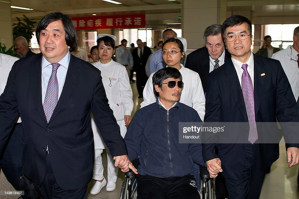 In this handout photograph provided by the US Embassy Beijing press office Chinese dissident Chen Guangcheng holds hands with US Ambassador to China...