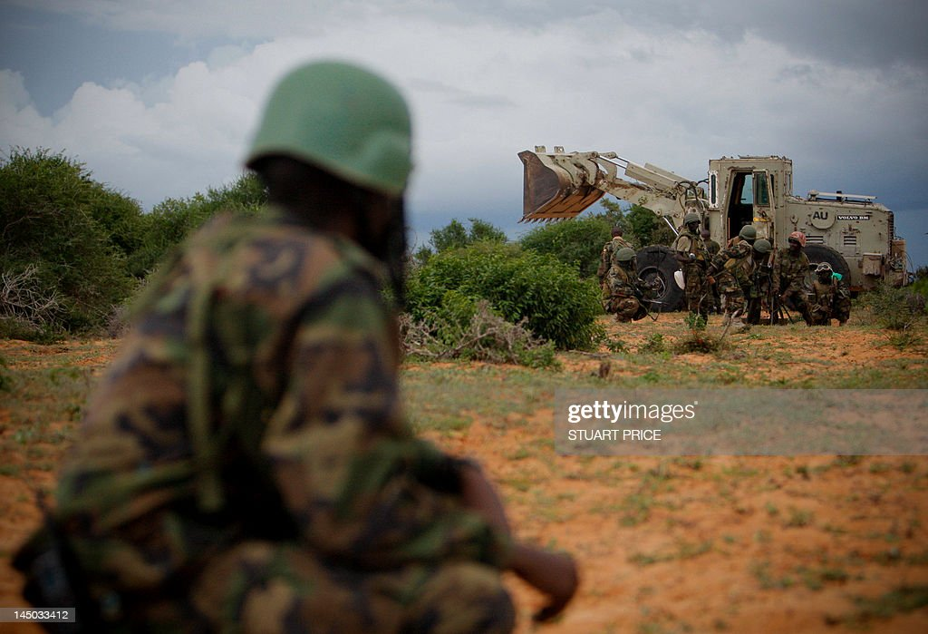 In this handout photograph released by the African Union-United Nations Support Team, a soldier serving with the African Union Mission in Somalia (AMISOM) looks on as an earth mover clears ground for a mortar team on May 22, 2012, during a joint AMISOM and Somali National Army (SNA) operation to seize and liberate territory from the Al-Qaeda-affiliated extremist group Al Shabaab in the Afgoye region west of Mogadishu. AMISOM Force Commander Lt. Gen Andrew Guti announced the beginning of 'Operation Free Shabelle' aimed at bringing security and econonic revival to the 400,000 people of the Afgoye Corridor and beyond in the Lower Shabelle region of Somalia, located to the south and west of the country's capital Mogadishu. RESTRICTED TO EDITORIAL USE - MANDATORY CREDIT 'AFP PHOTO/AMISOM/AU-UN / STUART PRICE' - NO