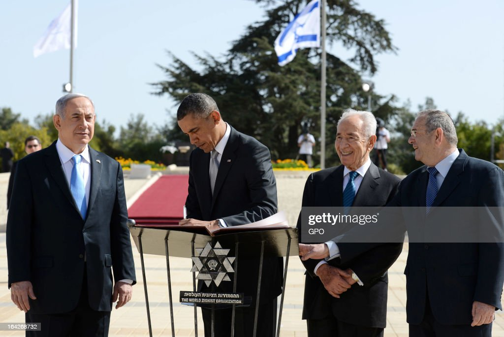 In this handout photograph supplied by the Government Press Office of Israel (GPO), U.S. President Barack Obama writes a message in the Mount Herzl visitor book next to Israel's Prime Minister Benjamin Netanyahu and President Shimon Peres during a visit to Mount Herzl on March 22, 2013 in Jerusalem, Israel. This is Obama's first visit as president to the region and his itinerary includes meetings with the Palestinian and Israeli leaders as well as a visit to the Church of the Nativity in Bethlehem.