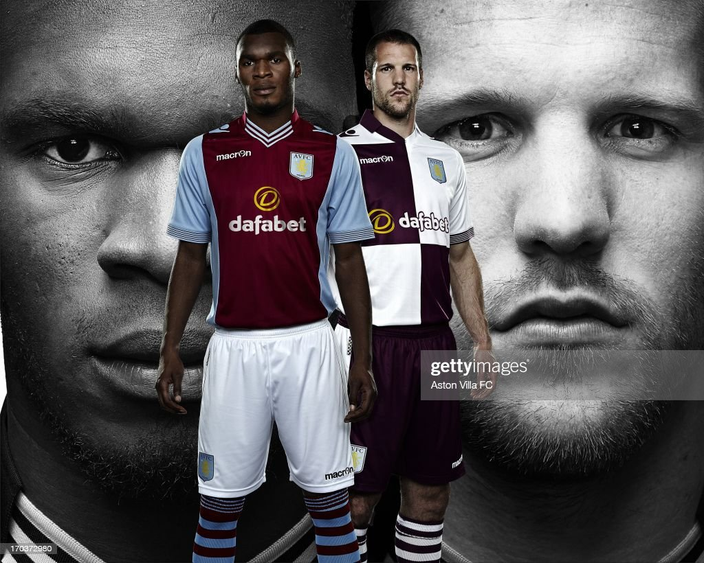 In this handout photographic illustration provided by Aston Villa, <a gi-track='captionPersonalityLinkClicked' href=/galleries/search?phrase=Ron+Vlaar&family=editorial&specificpeople=605352 ng-click='$event.stopPropagation()'>Ron Vlaar</a> and <a gi-track='captionPersonalityLinkClicked' href=/galleries/search?phrase=Christian+Benteke&family=editorial&specificpeople=4282509 ng-click='$event.stopPropagation()'>Christian Benteke</a> of Aston Villa wear the new Macron home and away kits for the 2013-14 season. Aston Villa and Macron are pleased to unveil the club's brand new home and away kits for the 2013-14 season. Both the home and away jerseys will offer players and fans a more slim-fit style from last season, offering maximum comfort. The home shirt retains the traditional look of Villa kits from past eras, closely resembling the shirt worn in the European Cup-winning season of 1981-82. The sleeves and collarbone of the home jersey have mesh inserts that give maximum breathability to the garment. The shirt also has a stylish striped v-neck collar and the reverse is embossed with the club's 'Prepared' motto. The away jersey is a modern design with white and blackcurrant quarters adorning both the front and the rear. This new cross-colour is also incorporated into the design of the collars and cuffs. The shirt retains a vintage collar with v-neck drop, ribbed striped cuffs, side flank micromesh inserts and club's 'Prepared' motto embossed onto the rear.
