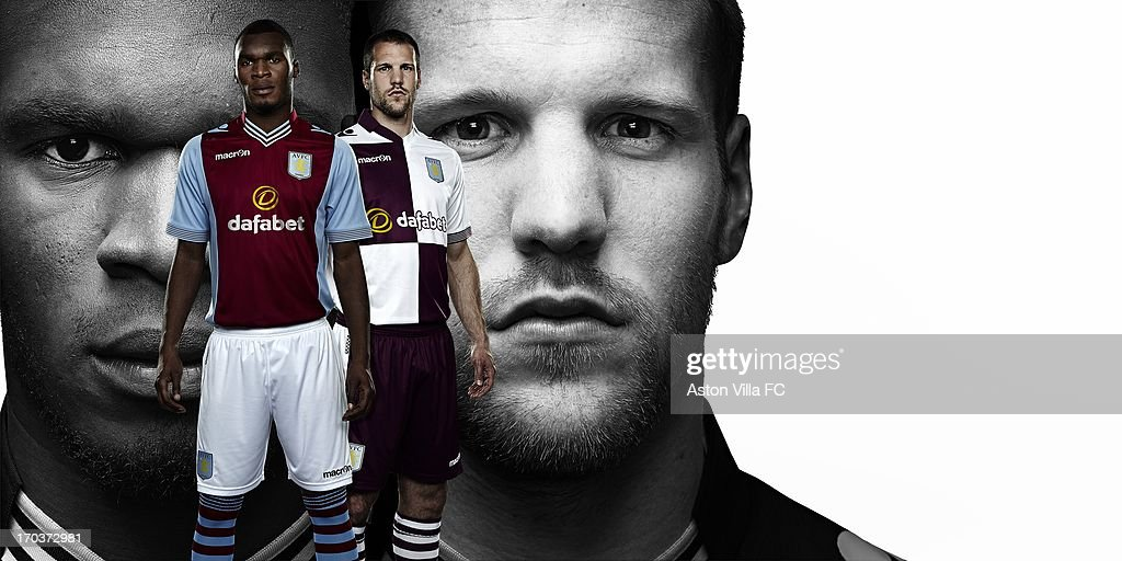 In this handout photographic illustration provided by Aston Villa, Ron Vlaar and Christian Benteke of Aston Villa wear the new Macron home and away kits for the 2013-14 season. Aston Villa and Macron are pleased to unveil the club's brand new home and away kits for the 2013-14 season. Both the home and away jerseys will offer players and fans a more slim-fit style from last season, offering maximum comfort. The home shirt retains the traditional look of Villa kits from past eras, closely resembling the shirt worn in the European Cup-winning season of 1981-82. The sleeves and collarbone of the home jersey have mesh inserts that give maximum breathability to the garment. The shirt also has a stylish striped v-neck collar and the reverse is embossed with the club's 'Prepared' motto. The away jersey is a modern design with white and blackcurrant quarters adorning both the front and the rear. This new cross-colour is also incorporated into the design of the collars and cuffs. The shirt retains a vintage collar with v-neck drop, ribbed striped cuffs, side flank micromesh inserts and club's 'Prepared' motto embossed onto the rear.