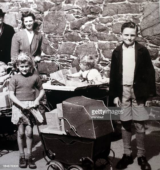 In this handout picture provided by The Red Cross David Isherwood poses with residents of Jersey receiving Red Cross parcels during the German...