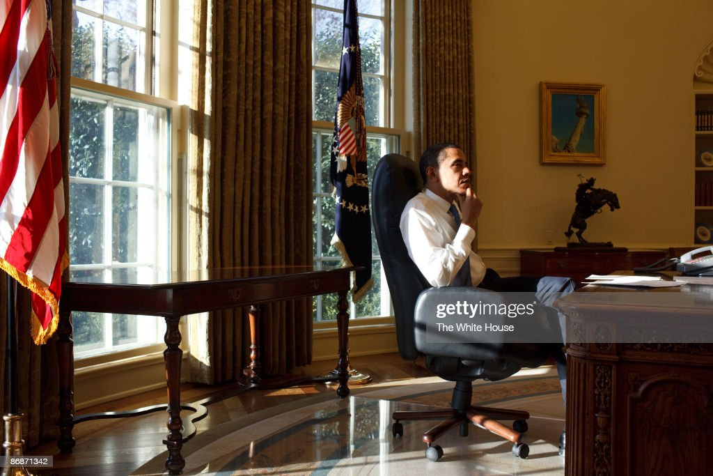 In this handout provide by the White House US President Barack Obama sits in the Oval Office of the White House the day after his inauguration on...