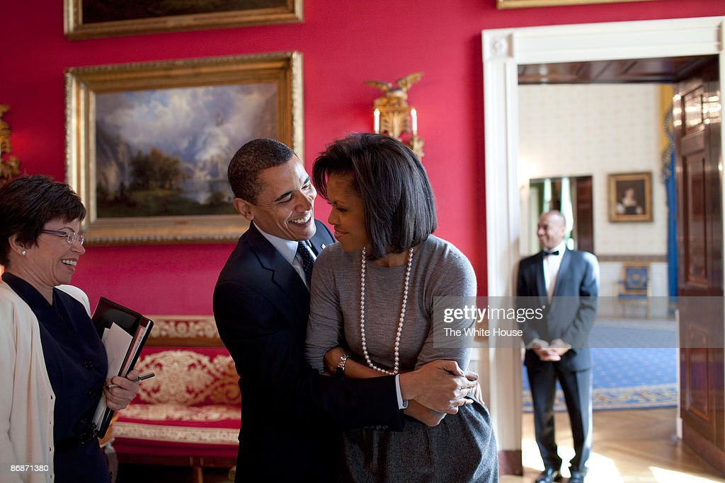 In this handout provide by the White House US President Barack Obama hugs First Lady Michelle Obama in the Red Room while Senior Advisor Valerie...