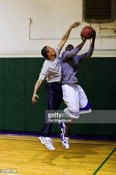 In this handout provide by the White House US President Barack Obama blocks a shot while playing basketball with personal aide Reggie Love at St...