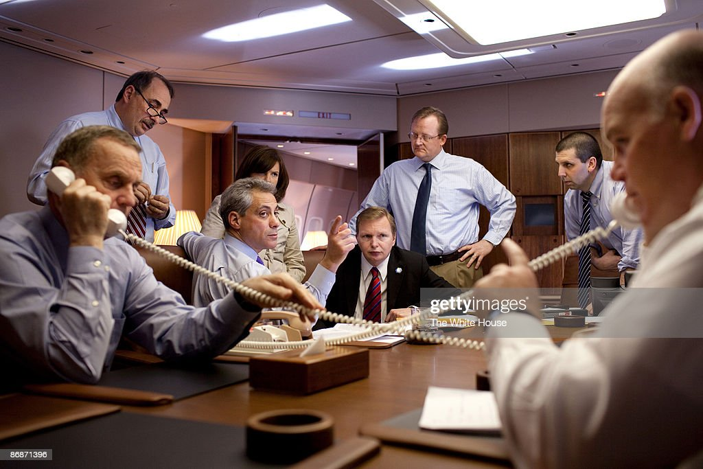 In this handout provide by the White House, U.S. President Barack Obama's Staff including Senior Advisor David Axelrod (2nd-L) looks on as National Security Advisor Gen. James 'Jim' Jones (L) talks on the phone, while Rahm Emanuel (3rd-L), and White House Press Secretary Robert Gibbs (6th-L) look on aboard Air Force One during the flight from Istanbul, Turkey to Baghdad, Iraq on April 7, 2009 in flight. Obama is serving as the 44th President of the U.S. and the first African-American to be elected to the office of President in the history of the United States.