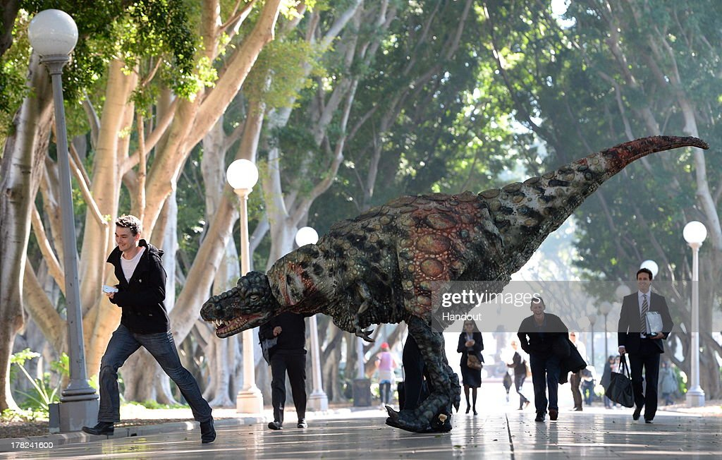 In this handout provided by Destination New South Wales, a Tyrannosaurus rex takes a morning stroll with commuters in Hyde Park on August 28, 2013 in Sydney, Australia. In a world first, the Australian Museum presents 'Tyrannosaurs: Meet the Family', an innovative, multimedia experience showcasing the newly-revised tyrannosaur family tree. With over 10 life-sized dinosaur specimens on display, including one of the oldest tyrannosaurs, Guanlong wucaii, the exhibition runs from 23 November 2013 to 27 July 2014. Showcasing a dramatic array of fossils and casts of tyrannosaur specimens, including neverbefore-seen specimens from China, 'Tyrannosaurs: Meet the Family' is designed to provide a snapshot of dinosaur life and show how this group became the world's top predators with their massive skulls, powerful jaws and bone-crunching teeth.