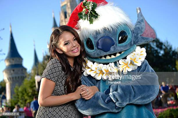 In this handout provided by Disney Parks Actress Janel Parrish one of the stars of 'Pretty Little Liars' on ABC Family poses with Stitch from Disneys...