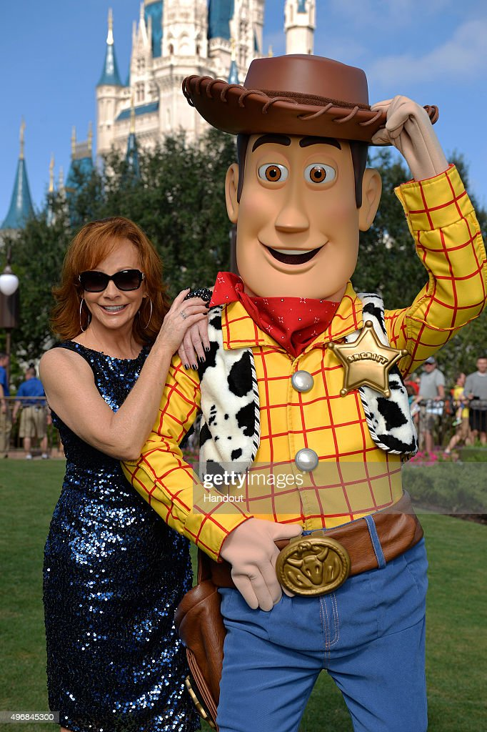 In this handout provided by Disney Parks Reba McEntire poses with Woody from DisneyPixar 'Toy Story' during a break from taping the 'Disney Parks...