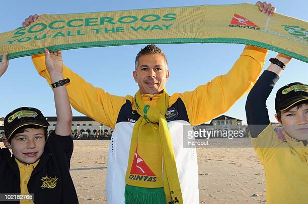 In this handout provided by James Morgan on behalf of MC Saatchi/Qantas former Socceroo and ALeague player Steve Corica holds aloft a giant support...
