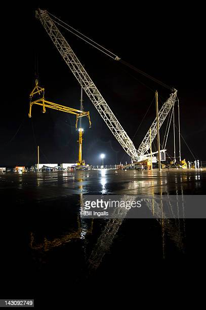 In this handout provided by NASA Cranes raise a sling in preparation for the demate of the Space Shuttle Discovery from the NASA 747 Shuttle Carrier...