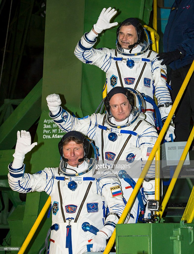 In this handout provided by NASA, Expedition 43 Russian Cosmonaut Mikhail Kornienko of the Russian Federal Space Agency (Roscosmos), top, NASA Astronaut Scott Kelly, center, and Russian Cosmonaut Gennady Padalka of Roscosmos wave farewell as they board the Soyuz TMA-16M spacecraft ahead of their launch to the International Space Station on March 27, 2015 in Baikonor, Kazakhstan. As the one-year crew, Kelly and Kornienko will return to Earth on Soyuz TMA-18M in March 2016.