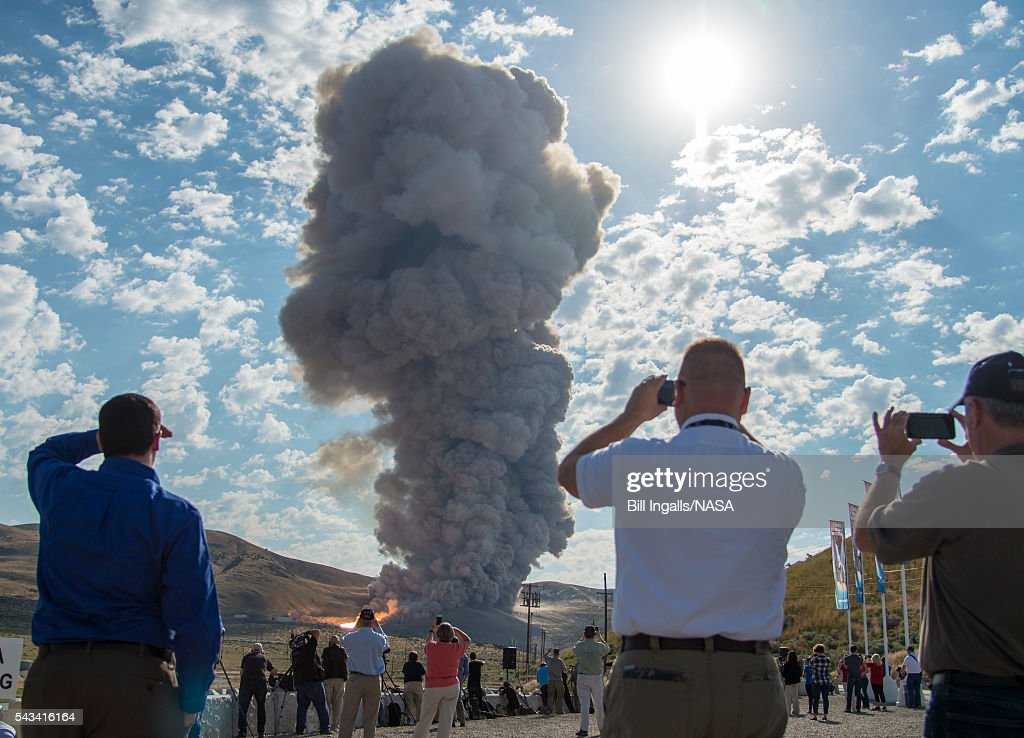 In this handout provided by NASA, guests watch the second and final qualification motor (QM-2) test for the Space Launch System's booster, Tuesday, June 28, 2016, at Orbital ATK Propulsion Systems test facilities in Promontory, Utah. During the Space Launch System flight the boosters will provide more than 75 percent of the thrust needed to escape the gravitational pull of the Earth, the first step on NASA's Journey to Mars.