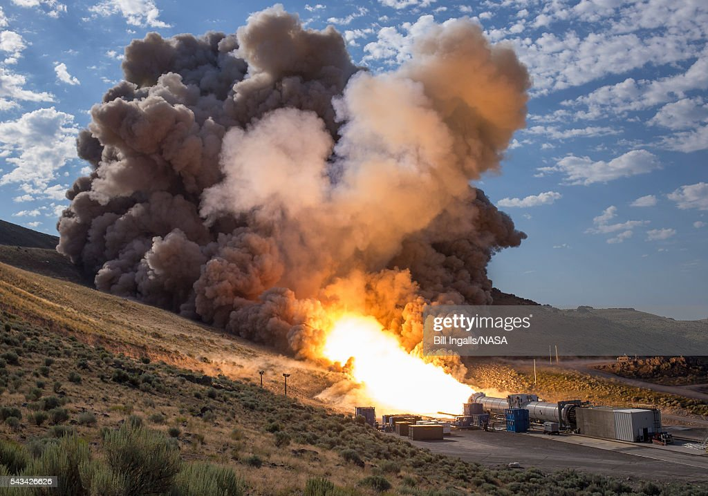 In this handout provided by NASA, The second and final qualification motor (QM-2) test for the Space Launch Systemâs booster is seen, Tuesday, June 28, 2016, at Orbital ATK Propulsion Systems test facilities in Promontory, Utah. During the Space Launch System flight the boosters will provide more than 75 percent of the thrust needed to escape the gravitational pull of the Earth, the first step on NASAâs Journey to Mars.