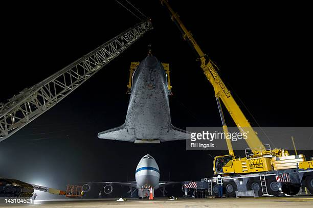 In this handout provided by NASA the space shuttle Discovery is suspended from a sling held by two cranes as the NASA 747 Shuttle Carrier Aircraft is...