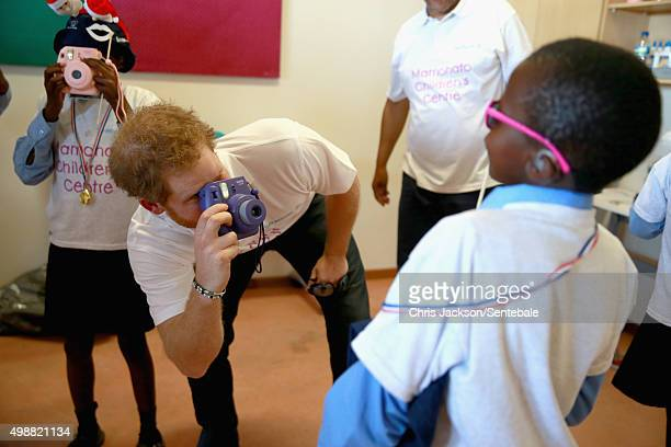 In this handout provided by Sentebale Prince Harry takes a photograph of a young boy using a Fuji Instax camera during a photography activity at the...