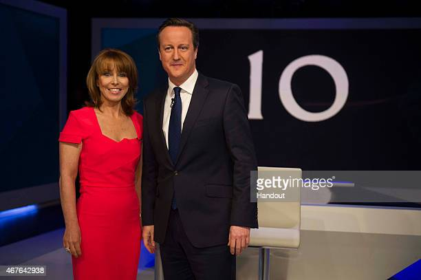 In this handout provided by Sky News Kay Burley of Sky News poses with British Prime Minister David Cameron ahead of the filming of 'Cameron Miliband...