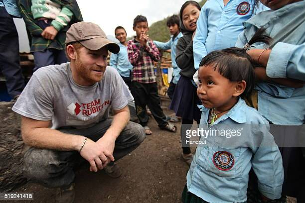 In this handout provided by Team Rubicon UK Prince Harry talks to a young boy during a visit to the Lapubesi temporary school site as he helps Team...