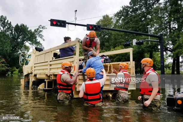 In this handout provided by the Army National Guard Texas National Guardsmen assist residents affected by flooding caused by Hurricane Harvey onto a...