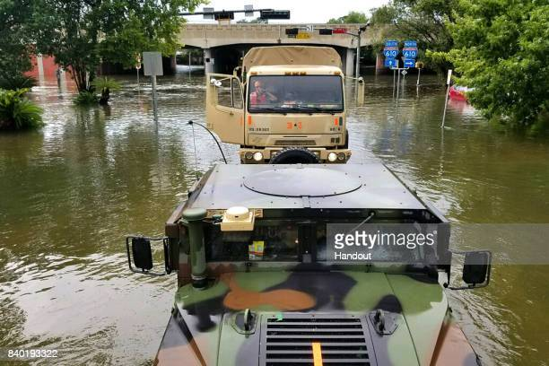 In this handout provided by the Army National Guard Texas National Guardsmen drive military vehicles down flooded streets while searching for...