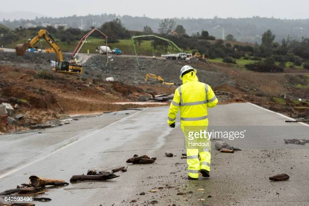 In this handout provided by the California Department of Water Resources aA worker walks down the damaged roadway near the Oroville Dam emergency...