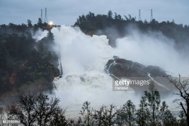 In this handout provided by the California Department of Water Resources Water continues to move down the damaged spillway at Oroville Dam with an...
