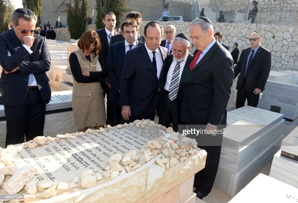 In this handout provided by the GPO, Israeli Prime Minister <a gi-track='captionPersonalityLinkClicked' href=/galleries/search?phrase=Benjamin+Netanyahu&family=editorial&specificpeople=118594 ng-click='$event.stopPropagation()'>Benjamin Netanyahu</a> (R) and French President Francois Hollande (C) lay tributes to the victims of the Toulouse attack at their graves in Givat Shaul on November 19, 2013 in Jerusalem, Israel. Francois Hollande is on a three day official visit to Israel and the West Bank.