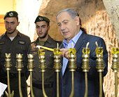 In this handout provided by the Israeli Government Press Office Israel Prime Minister Benjamin Netanyahu lights menorah candles on the fifth night of...