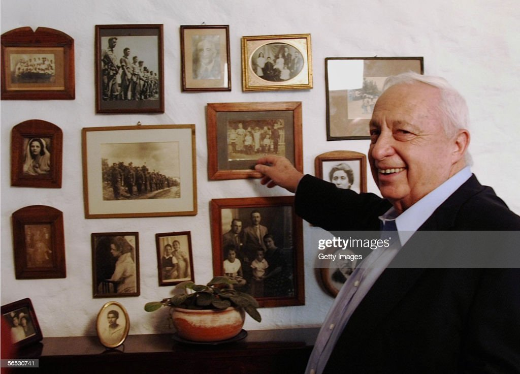 In this handout provided by the Israeli Governmental Press Office Israeli Prime Minister Ariel Sharon points to family photos at his home August 3...
