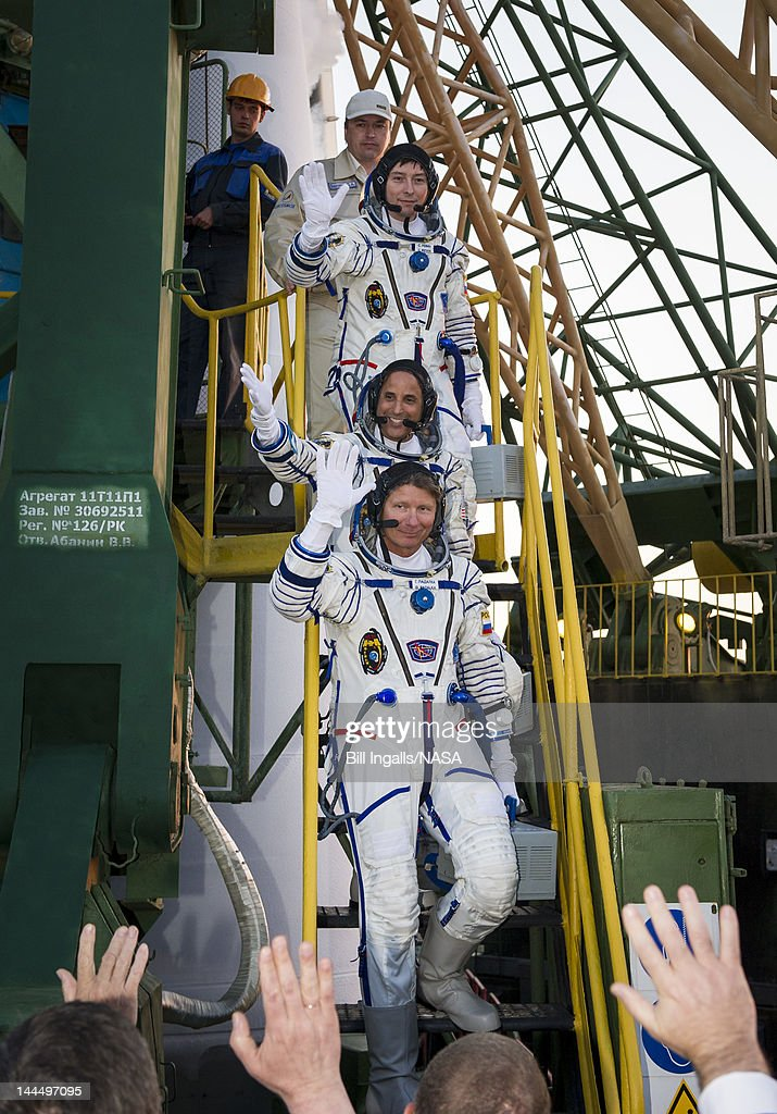 In this handout provided by the National Aeronautics and Space Administration (NASA), Expedition 31 Soyuz Commander Gennady Padalka, bottom, NASA Flight Engineer Joseph Acaba and Flight Engineer Sergei Revin, top, wave farewell from the base of the Soyuz rocket on May 15, 2012 at the Baikonur Cosmodrome in Kazakhstan. The launch of the Soyuz spacecraft with Padalka, Revin, and Acaba is scheduled for 9:01 a.m. local time on May 15.