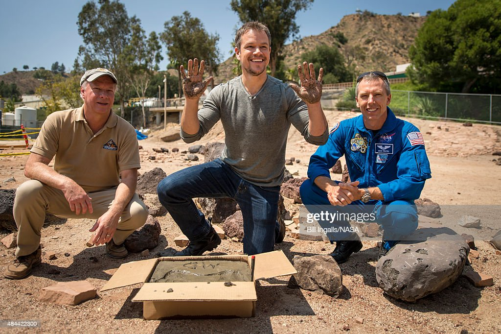 In this handout provided by the National Aeronautics and Space Administration (NASA), Actor <a gi-track='captionPersonalityLinkClicked' href=/galleries/search?phrase=Matt+Damon&family=editorial&specificpeople=202093 ng-click='$event.stopPropagation()'>Matt Damon</a>, who stars as NASA Astronaut Mark Watney in the film 'The Martian,' smiles after having made his hand prints in cement at the Jet Propulsion Laboratory (JPL) Mars Yard, while Mars Science Lab Project Manager Jim Erickson, left, and NASA Astronaut Drew Feustel look on, August 18, 2015, at the United Artist Theater in La Canada Flintridge, California. NASA scientists and engineers served as technical consultants on the film. The movie portrays a realistic view of the climate and topography of Mars, based on NASA data, and some of the challenges NASA faces as we prepare for human exploration of the Red Planet in the 2030s.