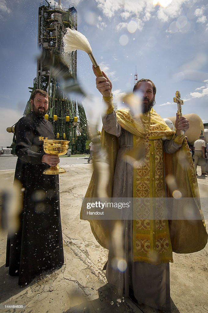 In this handout provided by the National Aeronautics and Space Administration (NASA), an Orthodox priest blesses members of the media shortly after blessing the Soyuz rocket at the Baikonur Cosmodrome Launch pad on May 14, 2012 in Baikonur, Kazakhstan. The launch of the Soyuz spacecraft with Expedition 31 crew members Soyuz Commander Gennady Padalka, Flight Engineer Sergei Revin of Russia and prime NASA Flight Engineer Joe Acaba is scheduled for launch at 9:01 a.m. local time on Tuesday, May 15, 2012.