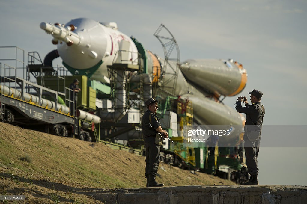 In this handout provided by the National Aeronautics and Space Administration (NASA), Russian security team members stop to take a photo as the Soyuz TMA-04M spacecraft is rolled out by train to launch pad one at the Baikonur Cosmodrome on May 13, 2012 in Baikonur, Kazakhstan. The Soyuz TMA-04M spacecraft will carry Soyuz Commander Gennady Padalka, Flight Engineer Sergei Revin of Russia and prime NASA Flight Engineer Joe Acaba, who are the crew of Expedition 31. The launch is scheduled for 9:01 a.m. local time on May 15, 2012