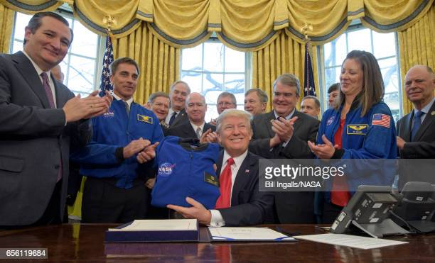 In this handout provided by the National Aeronautics and Space Administration President Donald Trump center holds a NASA flight jacket presented to...