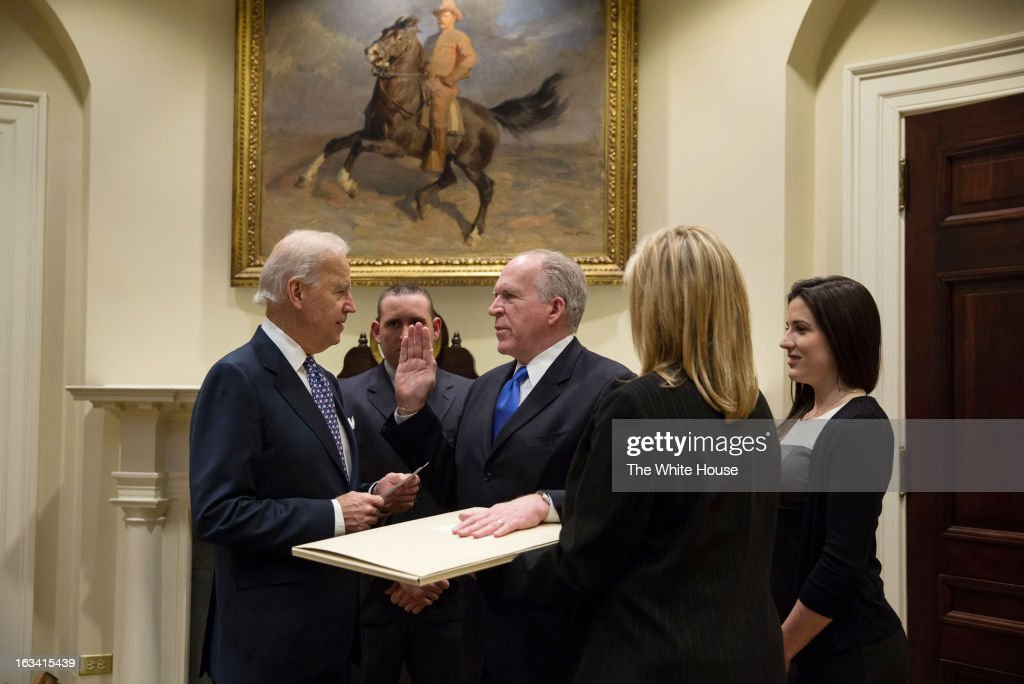 In this handout provided by the The White House, U.S. Vice President Joe Biden (L) swears in John Brennan as CIA Director in the Roosevelt Room of the White House, March 8, 2013 in Washington, DC. Brennan was sworn in with his hand on an original draft of the Constitution that has George Washington's personal handwriting and annotations on it, dating from 1787. Members of Brennan's family stand with him.