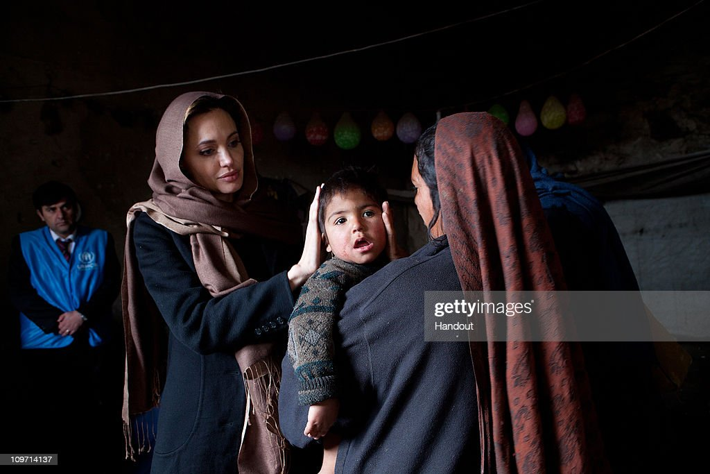 In this handout provided by the UNHCR, UNHCR Goodwill Ambassador, Angelina Jolie, meets with Khanum Gul, 35, a mother of 8 and her youngest son, Samir at their makeshift home at Tamil Mill Bus site February 2011, in Kabul city, Afghanistan. When Angelina last visited Khanum Gul, Samir was a newly born baby of 14 days, now he's two and a half years old, but having medical problems. Tajik and Pashtun families live side by side without any major conflict at the Tamil Mill Bus site. Over 70 percent of the families are returnees from the period of 2002-2004 who were unable to achieve sustainable reintegration in their places of origin and subsequently drifted to Kabul City in search of work. A nearby school is accessible to the children but the poor economic circumstances of the many families oblige them to send their children out to work. Low levels of literacy, particularly amongst the women, limit their access to employment other than the lowest paid daily labour wage.