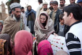 In this handout provided by the UNHCR UNHCR Goodwill Ambassador Angelina Jolie presents education materials to both local Headteacher Gul Rahman and...